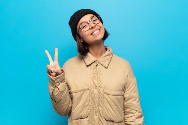 Giovane donna latina sorridente e dall'aspetto felice, spensierato e positivo, che indica vittoria o pace con una mano
