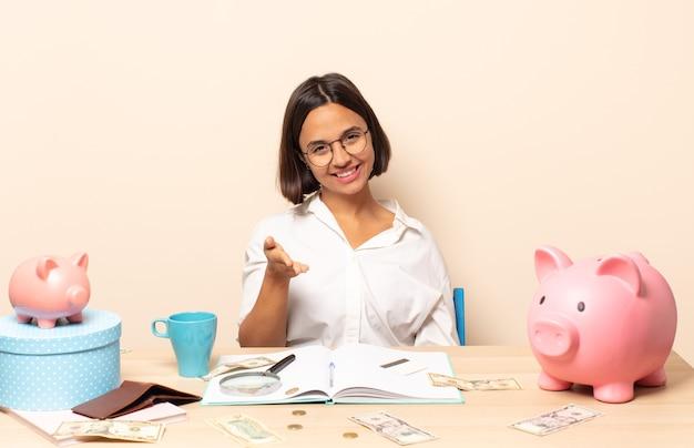 Giovane donna latina sorridente, dall'aspetto felice, fiducioso e amichevole, che offre una stretta di mano per concludere un affare, collaborando
