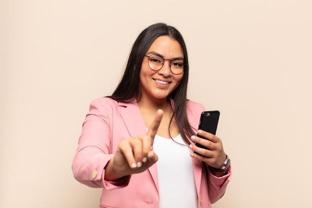 Giovane donna latina che sorride con orgoglio e sicurezza facendo posare trionfante il numero uno, sentendosi come un leader