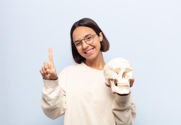 Giovane donna latina che sorride con orgoglio e sicurezza facendo la posa numero uno in modo trionfante, sentendosi come un leader
