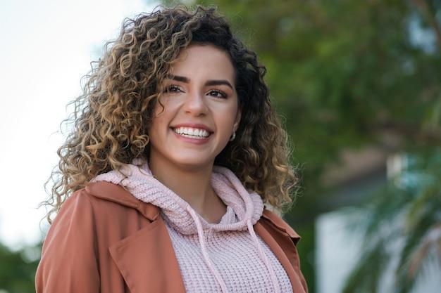 Giovane donna latina sorridente mentre si trova all'aperto per strada. concetto urbano.