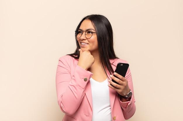 Giovane donna latina che sorride con un'espressione felice e sicura con la mano sul mento, chiedendosi e guardando di lato