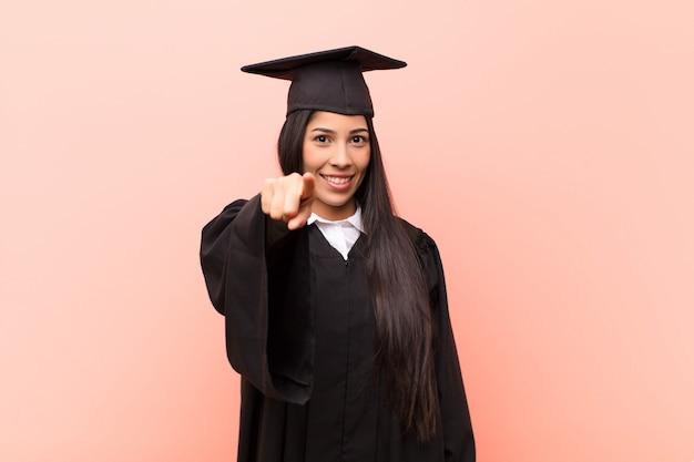 Giovane studentessa latina che indica con un sorriso soddisfatto, sicuro, amichevole, scegliendovi