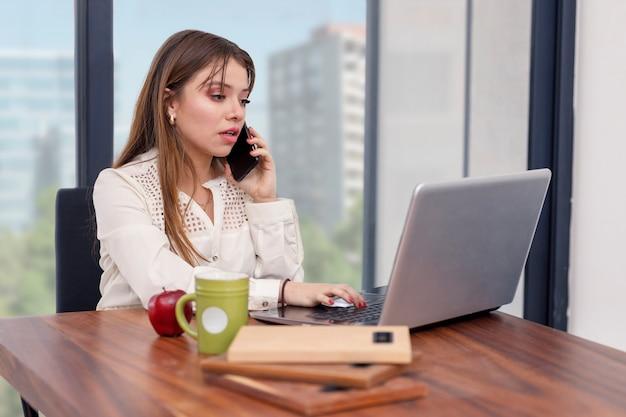 Giovane donna latina che parla al telefono mentre lavora da casa usando il cellulare e il laptop