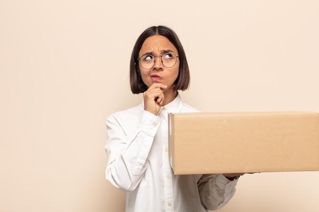 Giovane donna latina che pensa, si sente dubbiosa e confusa, con diverse opzioni, chiedendosi quale decisione prendere
