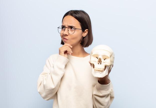 Giovane donna latina che pensa, si sente dubbiosa e confusa, con diverse opzioni