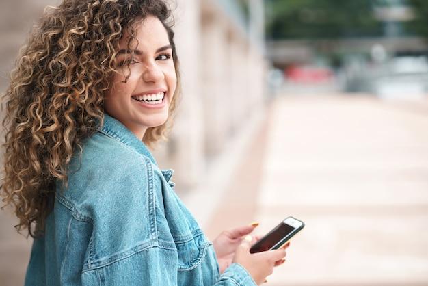 Giovane donna latina che utilizza il suo telefono cellulare mentre si trova all'aperto per strada. concetto urbano.