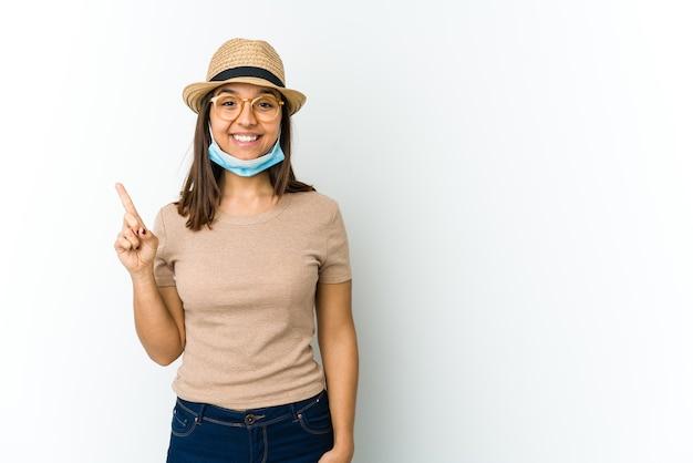 Giovane donna latina che indossa cappello e maschera per proteggere dal covid isolato su sfondo bianco che mostra il numero uno con il dito.