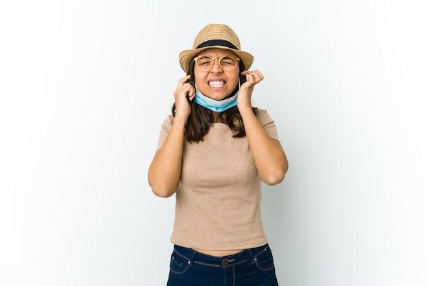Giovane donna latina che indossa un cappello e maschera per proteggere da covid isolato sulle orecchie del rivestimento murale bianco con le mani.