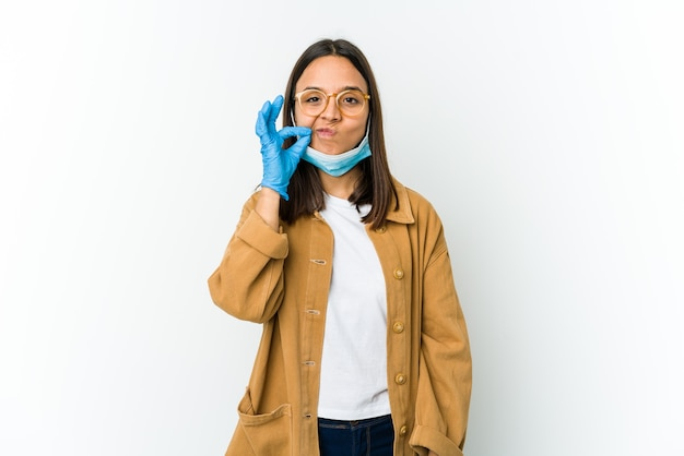 Giovane donna latina che indossa una maschera per proteggere da covid isolato su bianco con le dita sulle labbra mantenendo un segreto.