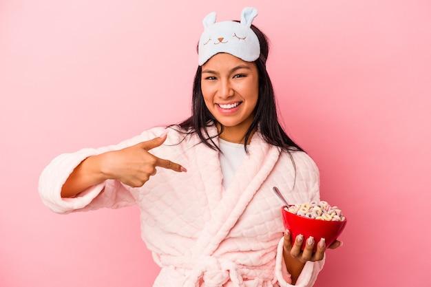 Giovane donna latina che indossa un pigiama con in mano una ciotola di cereali isolata su sfondo rosa persona che indica a mano uno spazio copia camicia, orgogliosa e sicura di sé