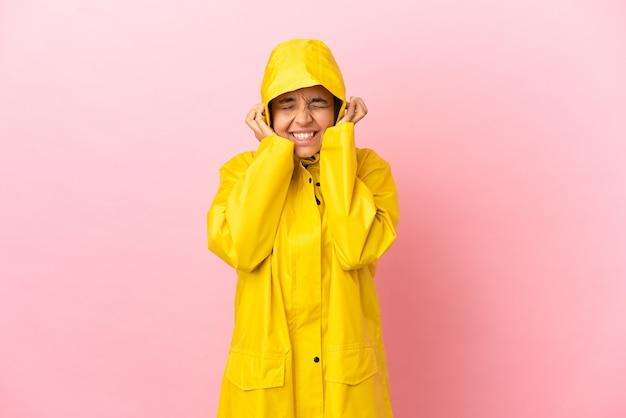 Giovane donna latina che indossa un cappotto antipioggia su sfondo isolato frustrato e che copre le orecchie