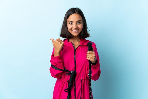 Giovane donna latina con zaino e bastoncini da trekking isolati su blu che punta di lato per presentare un prodotto