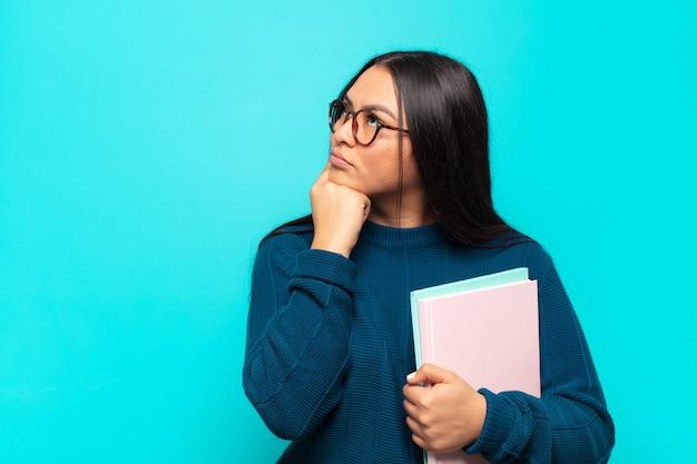 Giovane donna latina con uno sguardo concentrato, chiedendosi con un'espressione dubbiosa, guardando in alto e di lato