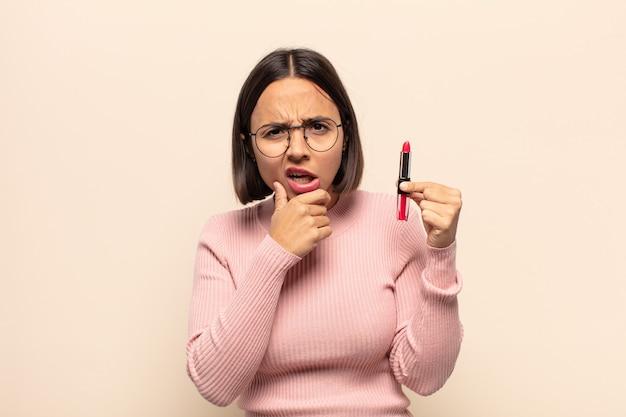 Giovane donna latina con la bocca e gli occhi spalancati e la mano sul mento, sentendosi spiacevolmente scioccata, dicendo cosa o wow