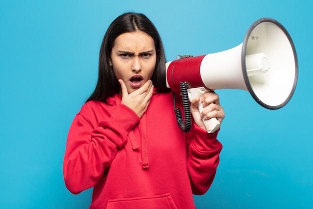 Giovane donna latina con la bocca e gli occhi spalancati e la mano sul mento, che si sente spiacevolmente scioccata