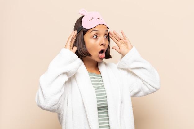 Giovane donna latina con la bocca aperta, che sembra inorridita e scioccata a causa di un terribile errore, alzando le mani alla testa