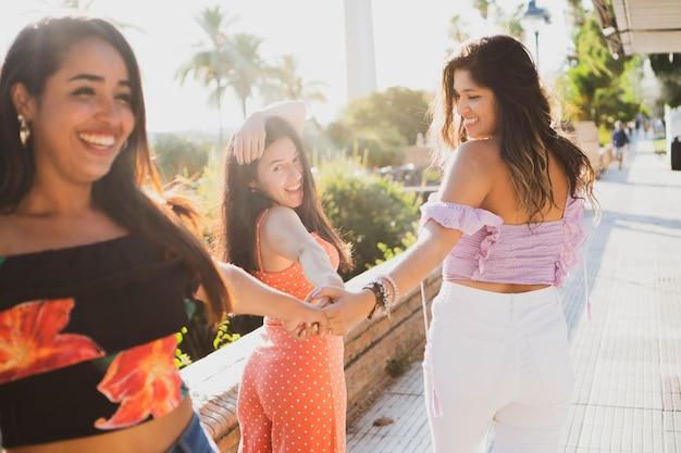 Giovani donne latine che camminano lungo il fiume ridendo ragazze che trascorrono una giornata di sole divertendosi all'aperto
