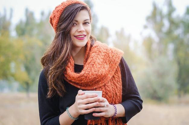 Giovane ragazza che ride con una tazza di caffè (tè) per una passeggiata nel parco all'aperto. tempo autunnale.