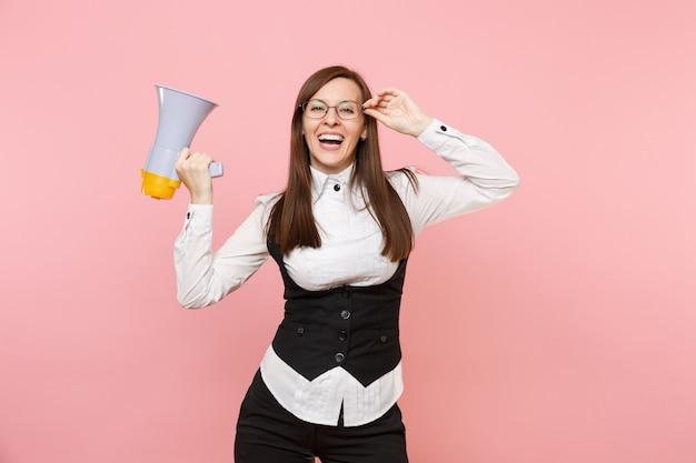 Giovane donna d'affari gioiosa ridente in abito nero, camicia e occhiali che tengono il megafono isolato su sfondo rosa pastello. signora capo. concetto di ricchezza di carriera di successo. copia spazio per la pubblicità.