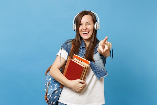 Giovane studentessa gioiosa di risata con le cuffie dello zaino che ascolta la musica della tenuta del libro di scuola che indica il dito indice sulla macchina fotografica isolata su fondo blu. istruzione al college universitario di scuola superiore.