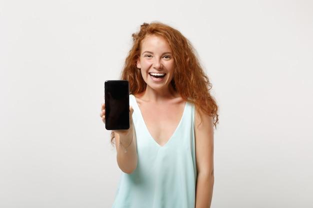 Giovane ragazza rossa di risata della donna in vestiti leggeri casuali che posano isolati su fondo bianco, ritratto dello studio. concetto di stile di vita della gente. mock up copia spazio. tenere il telefono cellulare con lo schermo vuoto vuoto.