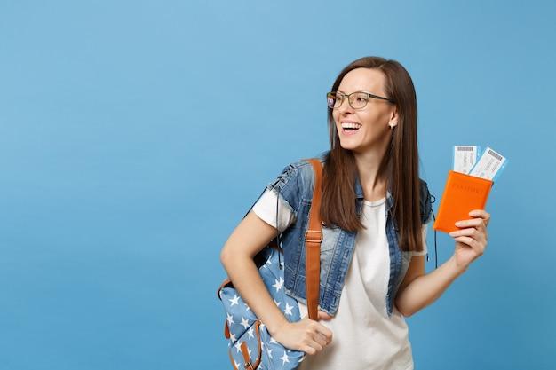 Giovane studentessa ridente con gli occhiali con lo zaino che guarda da parte tenere il passaporto, i biglietti della carta d'imbarco isolati su sfondo blu. istruzione in college universitario all'estero. concetto di volo di viaggio aereo.