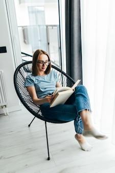 Giovane donna pigra a casa seduta su una sedia moderna davanti alla finestra che si rilassa nel suo soggiorno leggendo un libro