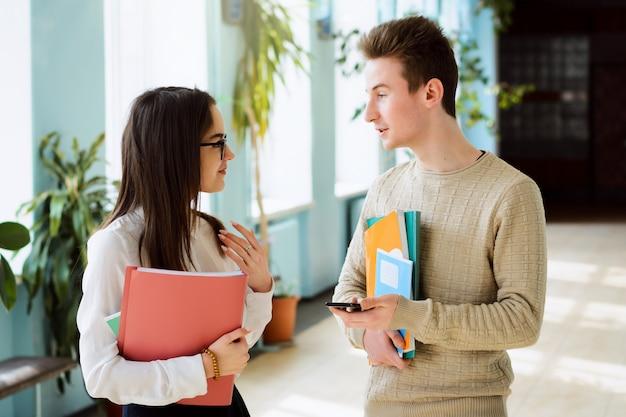 Giovani studenti in piedi nel corridoio della scuola a parlare e divertirsi insieme