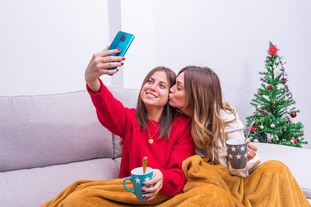 Giovani coppie lesbiche che bevono caffè, scattare foto e divertirsi vicino all'albero di natale. concetto di coppia lgbt, relax e vita domestica.