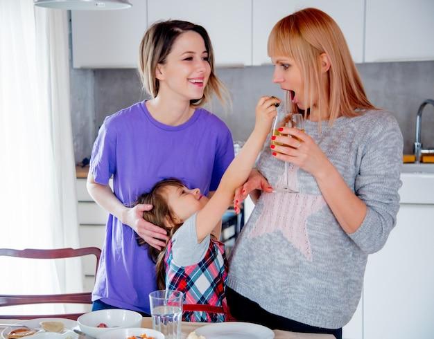 Giovane famiglia lesbica con una bambina in cucina.
