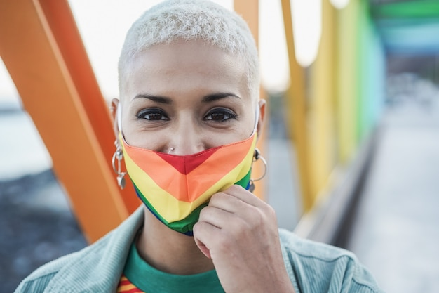 Giovane lesbica sorridente sulla fotocamera mentre indossa la maschera arcobaleno