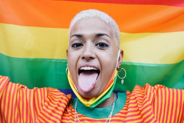 Giovane donna lesbica alla parata dell'orgoglio gay che tiene bandiera lgbt arcobaleno e guarda la telecamera - amore omosessuale e concetto lgbtqia