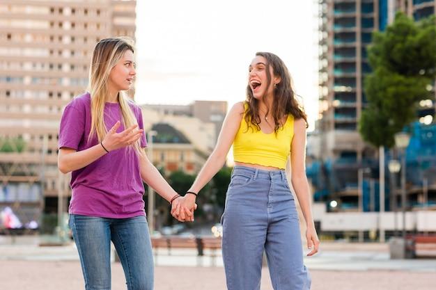 Una giovane coppia di donne lesbiche che si tiene per mano una femmina multietnica ispanica e caucasica insieme