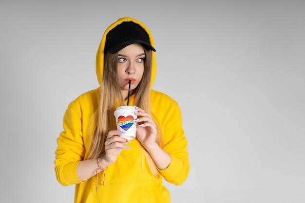 Giovane donna triste lgbtq che indossa una felpa con cappuccio gialla che tiene una tazza con cuore arcobaleno, su sfondo grigio