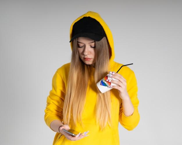 Giovane donna triste lgbtq che indossa una felpa con cappuccio gialla che tiene una tazza con cuore arcobaleno, guarda in uno smartphone, su sfondo grigio