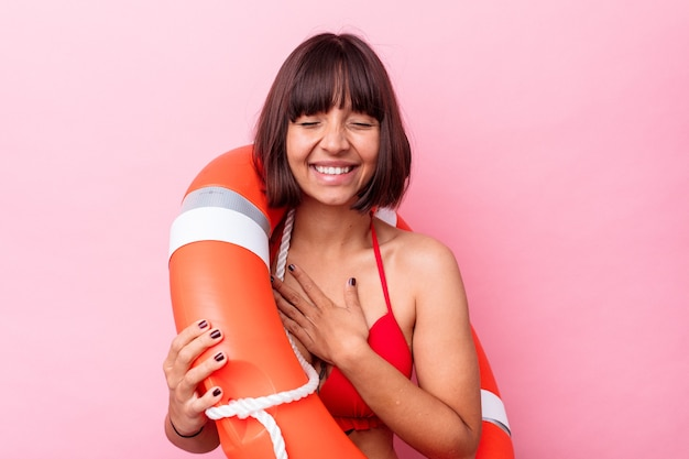 La giovane donna della corsa mista della guardia di vita isolata su fondo rosa ride ad alta voce tenendo la mano sul petto.