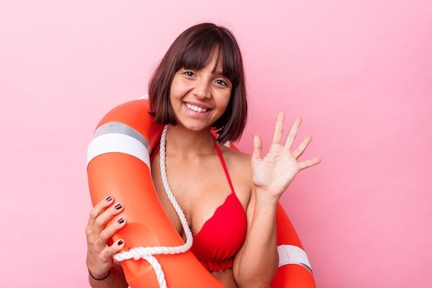 Giovane donna della corsa mista della guardia di vita isolata su fondo rosa sorridente allegro che mostra il numero cinque con le dita.