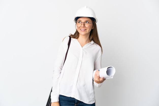 Giovane donna dell'architetto lituano con il casco e che tiene i modelli isolati su fondo bianco che pensa un'idea mentre osserva in su