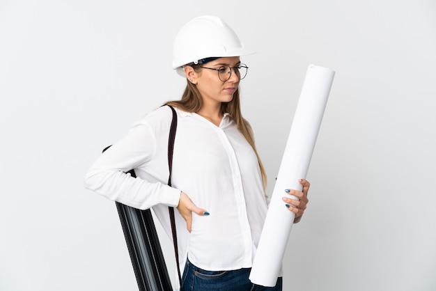 Giovane donna architetto lituana con casco e cianografie in possesso di isolati sul muro bianco che soffrono di mal di schiena per aver fatto uno sforzo