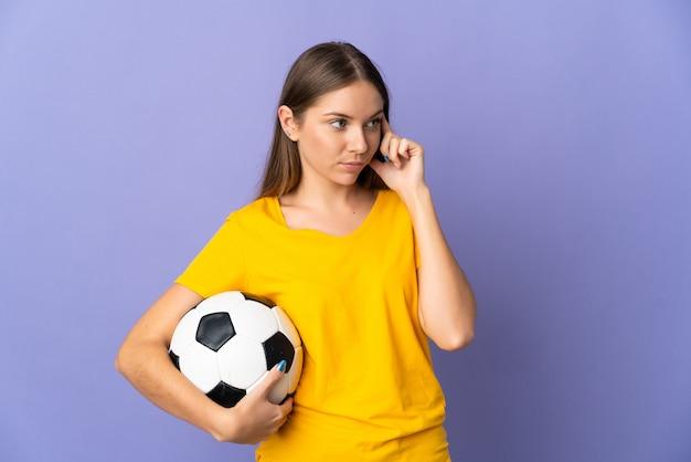 Donna giovane giocatore di football lituano isolata sulla parete viola che ha dubbi e che pensa