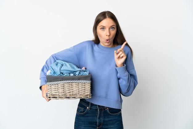 La giovane donna lituana che tiene un cesto di vestiti isolato su una superficie bianca con l'intenzione di realizzare la soluzione mentre solleva un dito