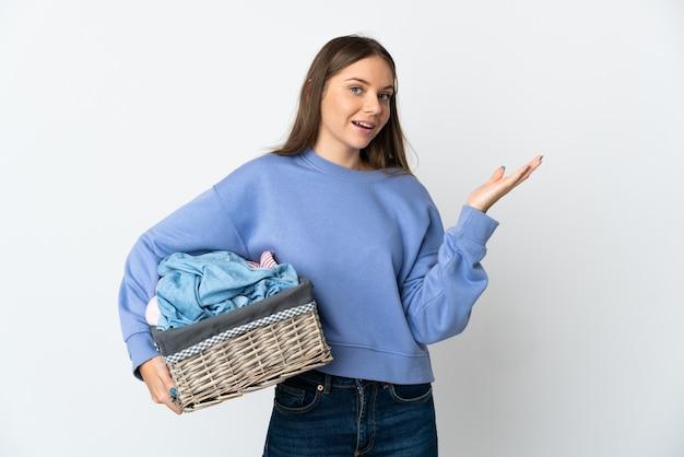 Giovane donna lituana che tiene un cesto di vestiti isolato sul muro bianco che estende le mani di lato per invitare a venire