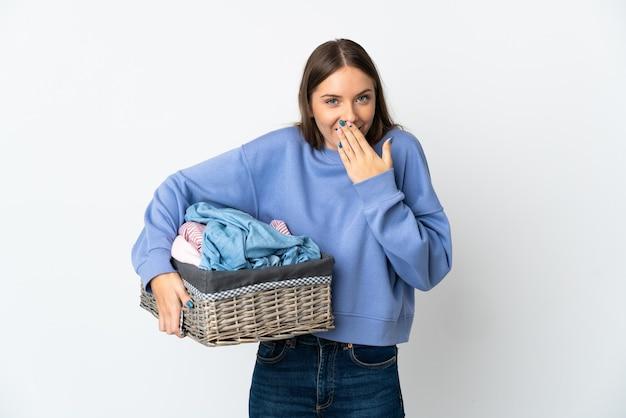 Giovane donna lituana che tiene un cesto di vestiti isolato sulla parete bianca felice e sorridente che copre la bocca con la mano