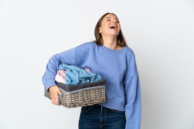 Giovane donna lituana che tiene un cestino dei vestiti isolato sulla risata bianca della parete