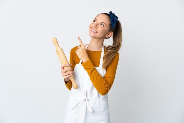 Giovane donna lituana che tiene un mattarello isolato su sfondo bianco che punta con il dito indice una grande idea