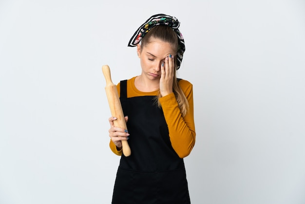 Giovane donna lituana che tiene un mattarello isolato su sfondo bianco con mal di testa
