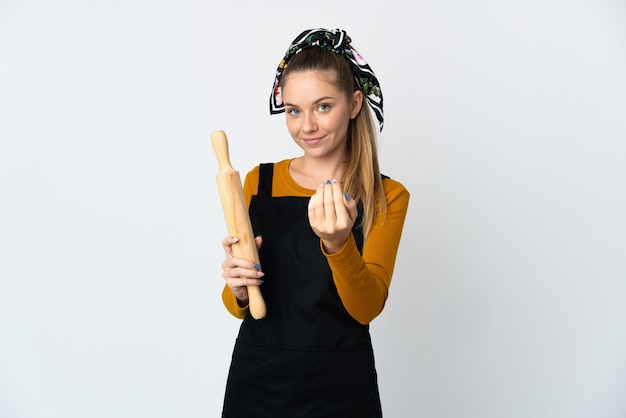 Giovane donna lituana che tiene un mattarello isolato sul muro bianco che invita a venire con la mano. felice che tu sia venuto
