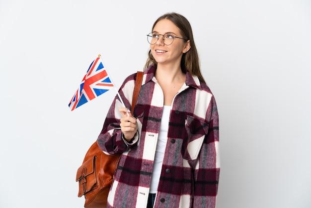 Giovane donna lituana che tiene una bandiera del regno unito isolata su priorità bassa bianca che pensa un'idea mentre osserva in su