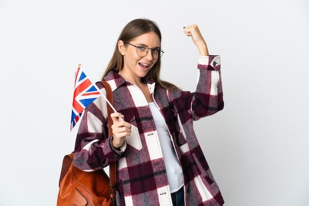 Giovane donna lituana che tiene una bandiera del regno unito isolata sulla parete bianca che fa un gesto forte Foto Premium